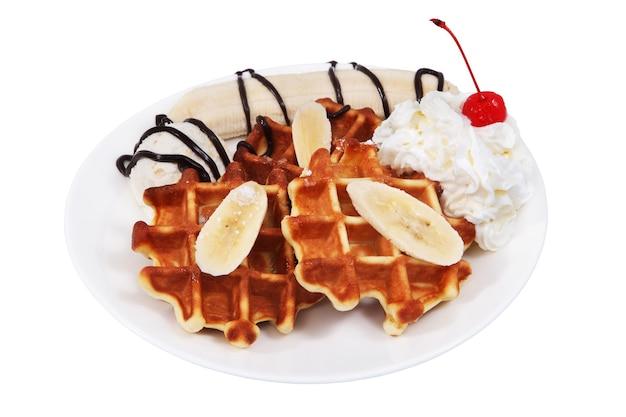 Dessert mit belgischen waffeln, eis, schlagsahne und einer scheibe banane ist auf teller, isoliert auf weißem hintergrund, kein körper.