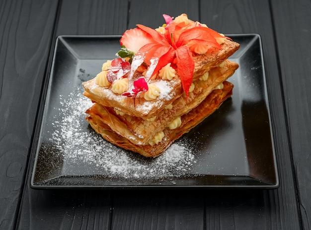 Dessert mit blätterteig, sahne und erdbeeren auf einer schwarzen oberfläche