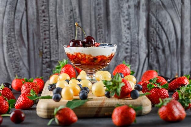Dessert mit erdbeere, blaubeere, kirsche, schneidebrett in einer vase auf grauer und hölzerner oberfläche, seitenansicht.