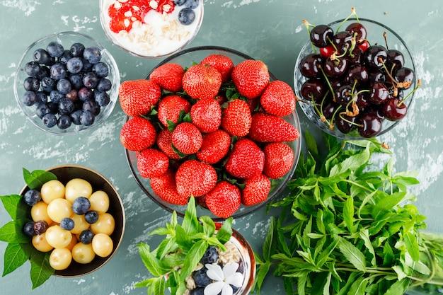 Dessert mit erdbeeren, blaubeeren, minze, kirschen in vase und becher auf gipsoberfläche, flach gelegt.
