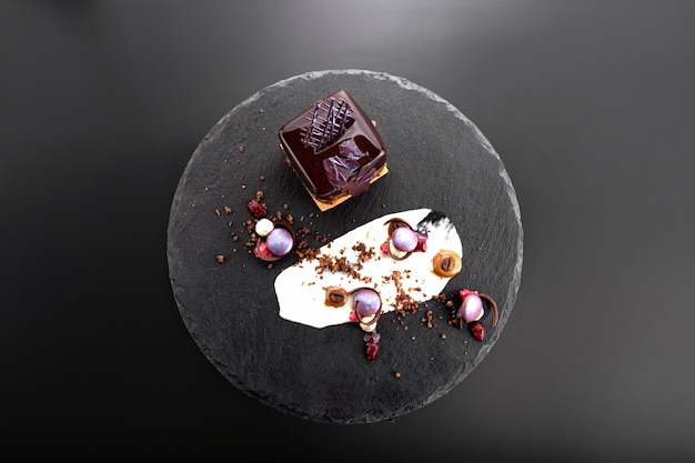 Dessert mit nüssen in schokoladenglasur in form eines würfels auf schwarzem schiefer
