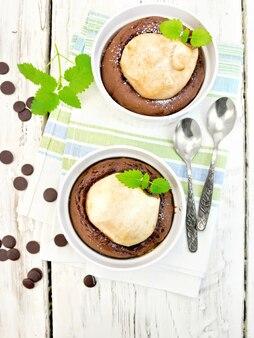 Dessert mit zwei weißen schüsseln mit schokolade und birne, löffel, minze auf einem handtuch auf dem hintergrund der holzbretter oben