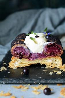 Dessert saint onore. beerenkuchen. blätterteigkuchen mit kränzchen, buttercreme, marmelade mit schwarzen johannisbeeren mit frischer minze, lavendelblüten und beeren. französisches gourmet-dessert auf grauer wand.