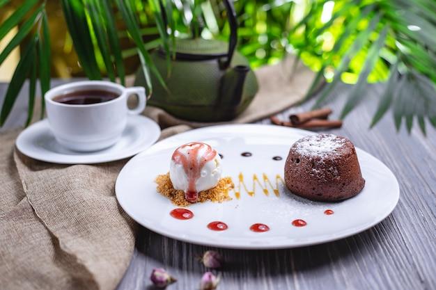Dessert-schokoladenfondant der vorderansicht mit eiscreme und einer tasse tee