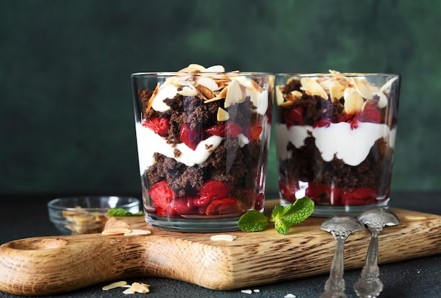 Dessert schwarzwald mit kirschen in einem glas auf einem holzbrett. traditionelles deutsches dessert.