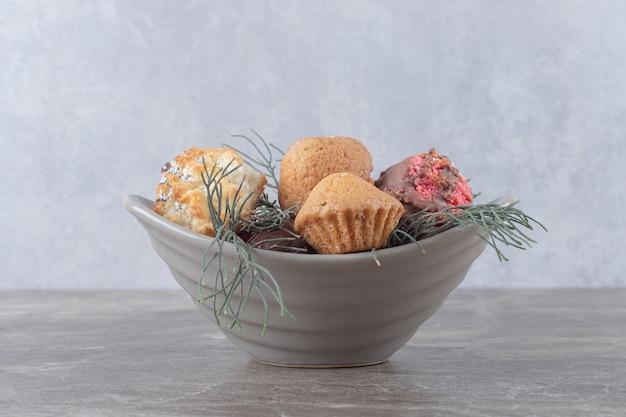 Dessert-sortiment auf einer kleinen, mit kiefernblättern geschmückten schale auf marmoroberfläche