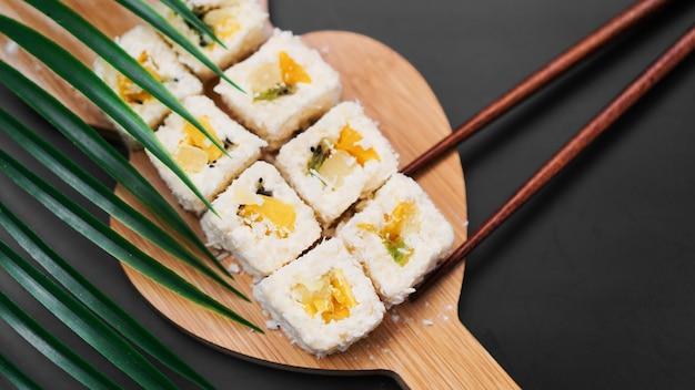 Dessert-sushi. süße kiwi, ananas-sushi-rollen. sushi auf einem holztablett auf schwarzem hintergrund. hält eine süße rolle mit holzstäbchen.