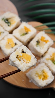 Dessert-sushi. süße kiwi, ananas-sushi-rollen. sushi auf einem holztablett auf schwarzem hintergrund mit einem tropischen blatt. vertikales foto