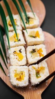Dessert-sushi. süße kiwi, ananas-sushi-rollen. sushi auf einem holztablett auf schwarzem hintergrund mit tropischem blatt. vertikales foto. hält eine süße rolle