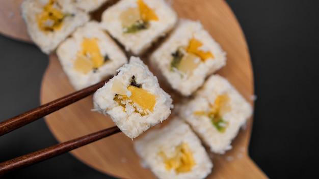 Dessert-sushi. süße kiwi-, ananas- und bananen-sushi-rollen. sushi auf einem holztablett auf schwarzem hintergrund mit einem tropischen blatt.