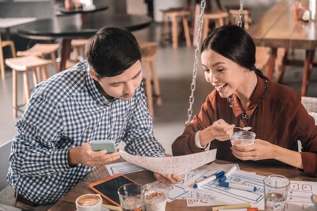 Dessert und arbeit. strahlende stilvolle frau, die ihr dessert isst und den gutaussehenden ehemann betrachtet, der arbeitet