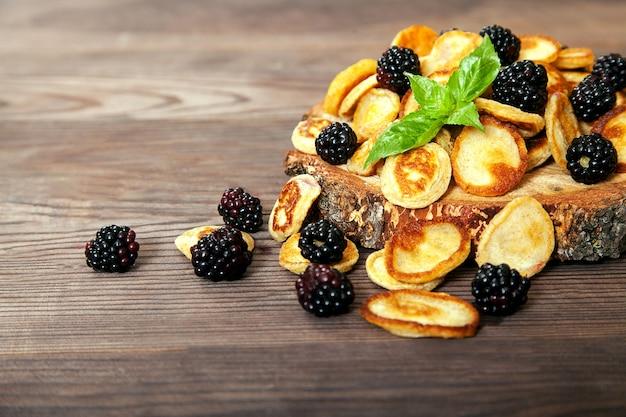 Dessert von mini-pfannkuchen und brombeeren mit einem minzblatt.