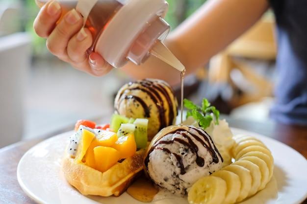 Dessert, waffeln mit gemischten früchten, bananenscheiben, eis mit honig