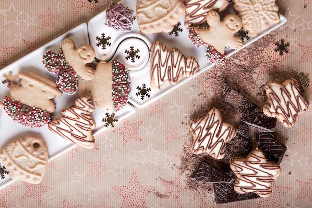Dessert zum teilen als familie zu weihnachten, weihnachtsplätzchen mit schokolade und farbigen samen, familienessen, weihnachtssnack mit freunden.