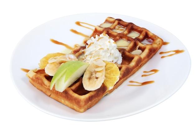 Dessertgericht, belgische waffel mit kondensmilch, schlagsahne und obstscheiben, banane, apfel, orange, auf teller gelegt.