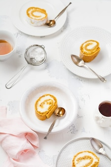 Dessertkürbisrolle mit buttercreme und orangenserver für den festlichen tisch auf hellgrauem tisch. selektiver fokus.