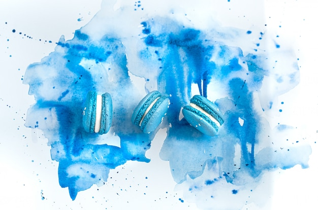 Dessertmakrone auf blauem aquarell, stilvolles kreatives.