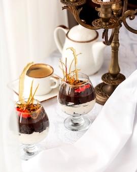 Desserts in glas mit vanillecreme und schokoladensauce und espresso