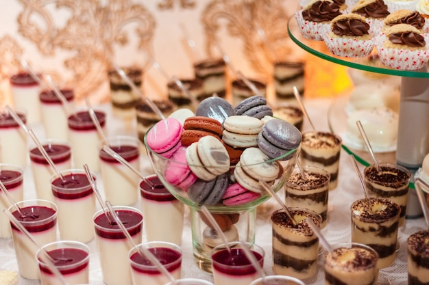 Desserts mit mousse, kekse. verschiedene arten von süßem gebäck, kleinen bunten süßen kuchen, macaron und anderen desserts am süßen buffet.