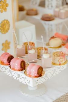 Desserts mit obst, mousse, gebäck. verschiedene arten von süßem gebäck, kleine bunte süße kuchen, macaron und andere desserts im süßen buffet. schokoriegel zum geburtstag.