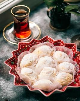Desserts mit zuckerpulver und schwarzem tee