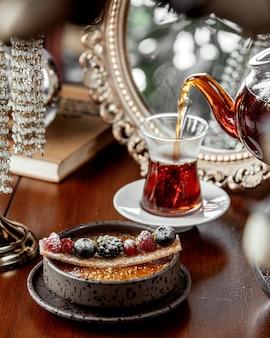 Dessertschale serviert mit schwarzem tee aus der teekanne gegossen