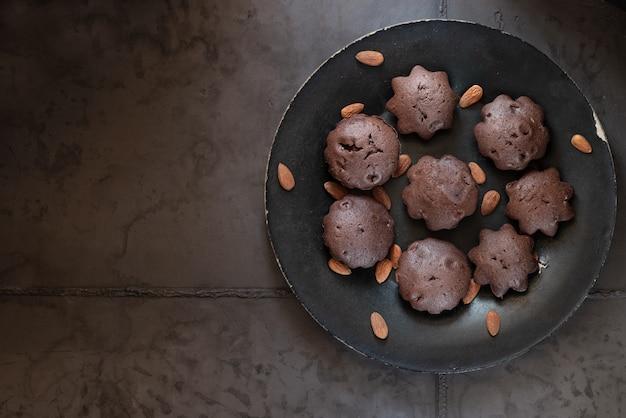 Dessertschokoladenmuffins auf einem schwarzen teller. grauer konkreter hintergrund