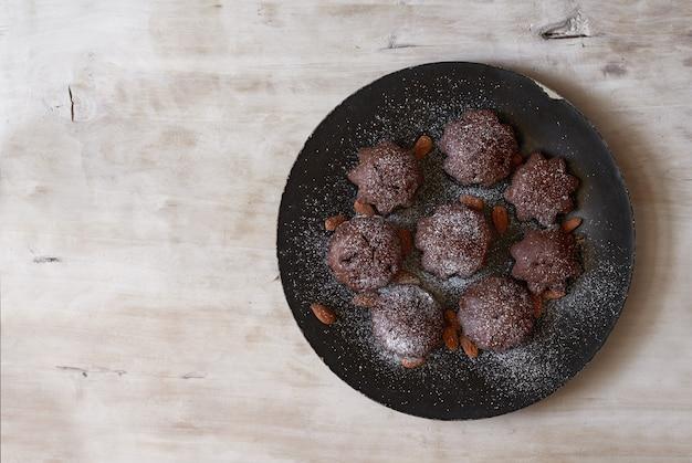 Dessertschokoladenmuffins auf einem schwarzen teller und einem hellen hölzernen hintergrund