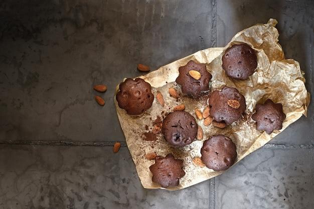 Dessertschokoladenmuffins auf pergamentpapier. grauer konkreter hintergrund