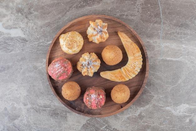 Dessertsortiment mit keksen, brötchen und cupcakes auf einem tablett auf marmoroberfläche
