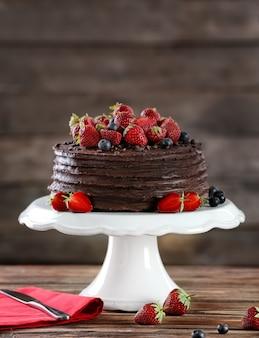 Dessertständer mit leckerem schokoladenkuchen auf holztisch