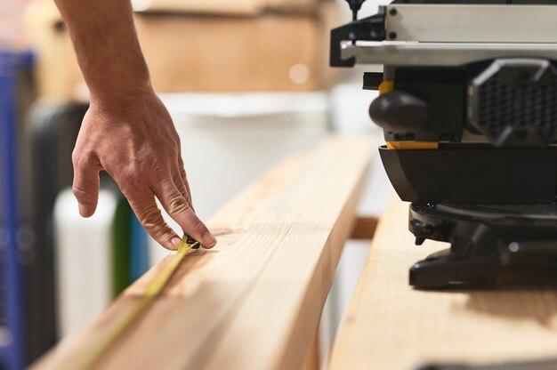 Detail der finger, die ein maßband auf einer werkbank halten