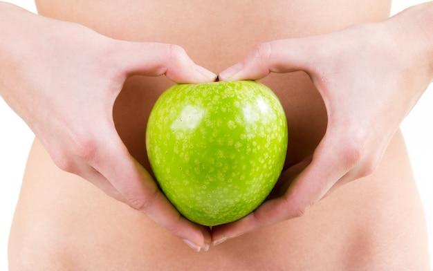 Detail der frau hände halten einen grünen apfel