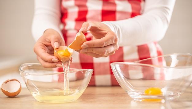 Detail der hände der frau, die eigelb vom weißen in zwei glasschüsseln trennen.