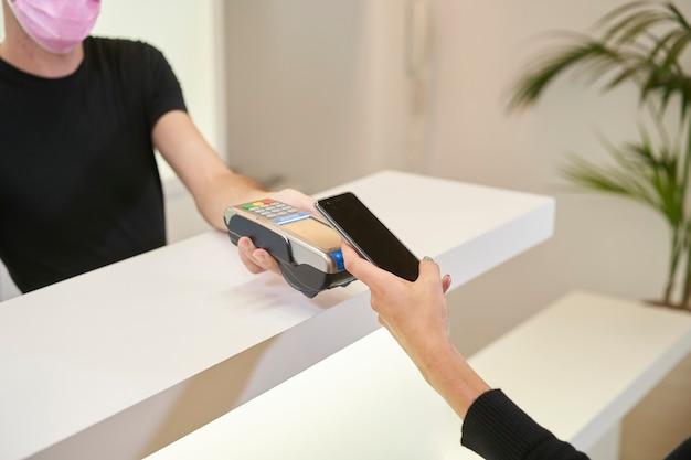 Detail der hände eines kunden, der mit dem smartphone in einer apotheke, einer gynäkologischen, zahnmedizinischen oder ästhetischen klinik zahlt. aus sicht des kunden.