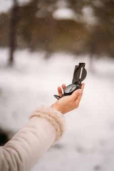Detail der hand einer frau, die einen kompass hält - vertikales bild