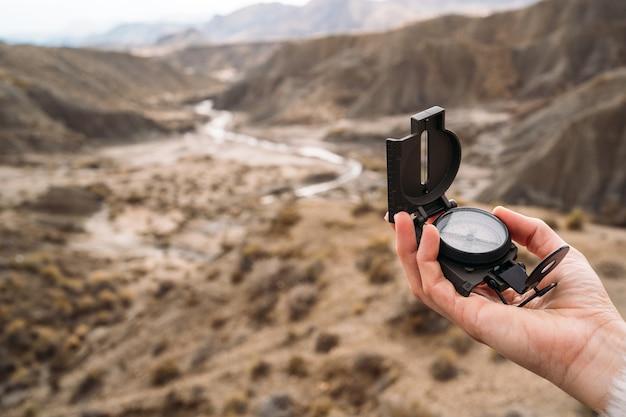 Detail der hand einer frau, die einen kompass mit der wüste im hintergrund hält - nahaufnahme