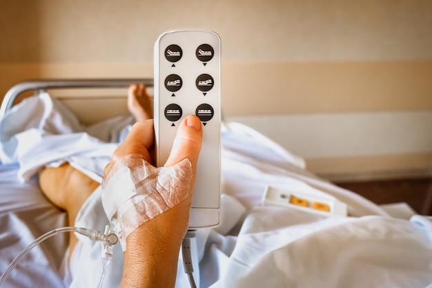 Detail der hand eines weiblichen krankenhauspatienten im bett unter verwendung des knopfes, um ihr bett in position zu bringen.