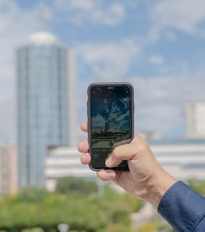 Detail der männlichen hand, die ein panoramafoto mit dem handy macht
