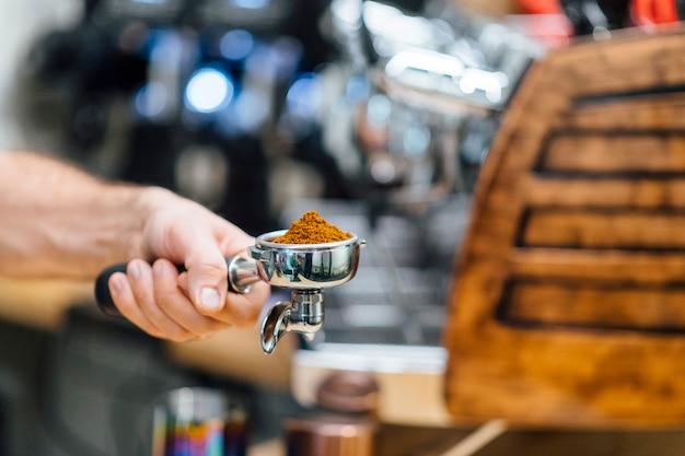 Detail der mannhand, die siebträgerempfänger hält, der mit kaffeepulver während der zubereitung des espressos gefüllt wird