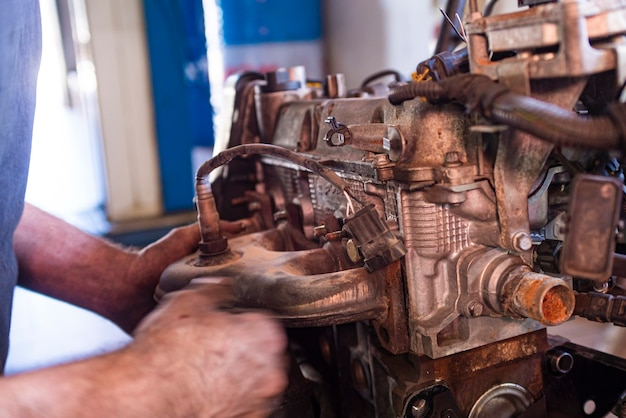 Detail der mechaniker überholt automotor in einer werkstatt