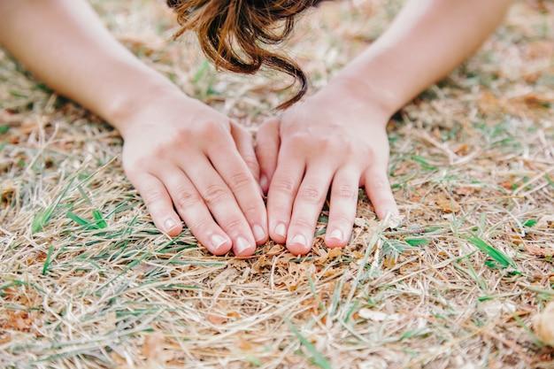 Detail der nicht erkennbaren handhände der frau, die den erdboden berühren. menschlicher kontakt mit dem naturkonzept. umweltprobleme und gesunder lebensstil. achtsamkeit lebensweise.