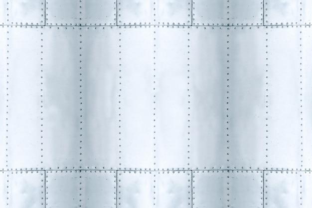 Detail des alten schmutzstückes der metallplatte mit bolzen, aluminiumoberflächenhintergrund