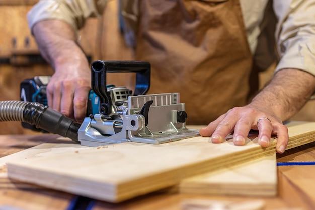 Detail des keksverbinders bei der arbeit auf einer sperrholzplatte