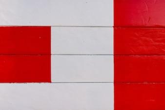 Detail des roten Kreuzes auf weißem Holztisch.