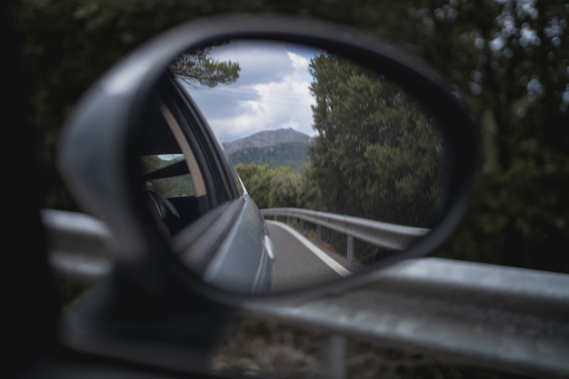 Detail des rückspiegels eines autos, das durch eine bergstraße fährt