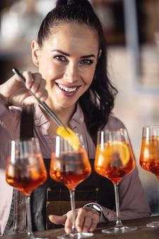 Detail einer barkeeperin, die einen orangenkeil in einen aperol-spritz-cocktail setzt.