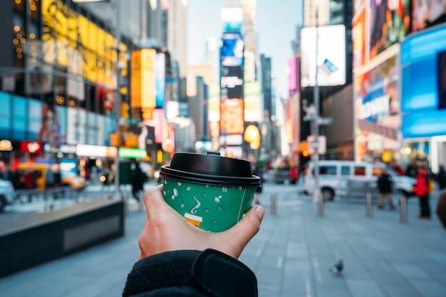 Detail einer hand, die ein grünes kaffeeglas mit new york city im hintergrund hält