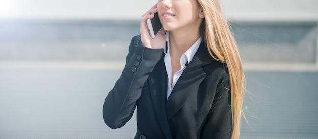 Detail einer jungen geschäftsfrau, die am handy spricht