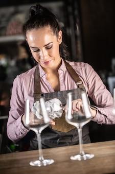 Detail einer kellnerin, die gläser in der bar putzt.
